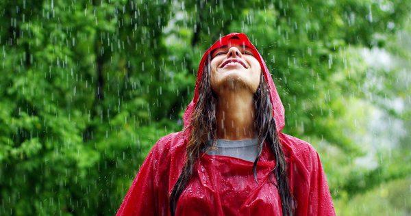 Lachende vrouw met rood regenpak in de regen